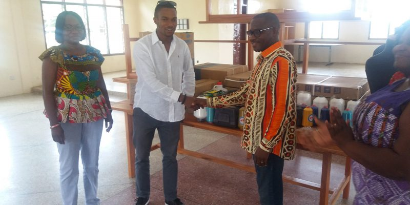 Mr Cromwell Awadey shaking hands with Mr. Jesse Nuno in appreciation of his kind gesture. Behind Jesse, is Mrs. Googie Nuno, his mother